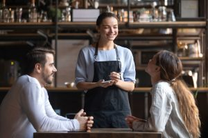 Happy restaurant employee with clients